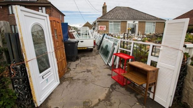 Residents are furious after a hoarder was given permission to carry on filling his front garden with old windows and doors. Photo: SWNS.com