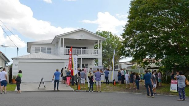 A large crowd of people gather for the auction of 50 Mellor Street, Kedron. Photo: Bradley Kanaris
