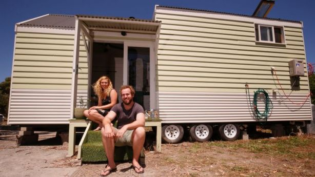 Ashleigh and Dan sit outside their tiny home. Photo: Darrian Traynor