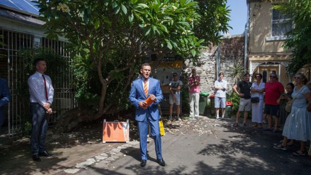 Auctioneer Damien Cooley took an opening bid of $2.1 million at the auction of 5 Darley Place, Darlinghurst. Photo: Fiona Morris