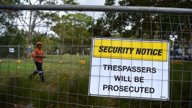 A man walks inside the fenced off area on the Euston Road side of Sydney Park. Photo: Kate Geraghty