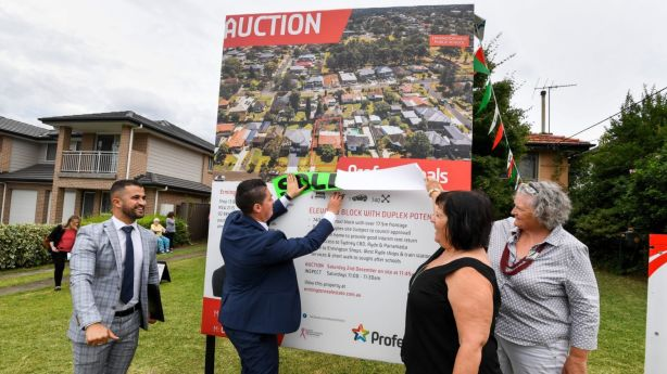 Sisters Jenny Lindsay and Louise Haverfield-Price help selling agents Paul Tassone and Ahmad Malas of Professionals Ermington put up the sold sticker for 17 Woodward Street. Photo: Peter Rae.