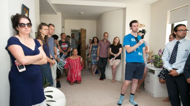 More than 20 people squeezed into the property to watch it go under the hammer. Photo: Steven Woodburn