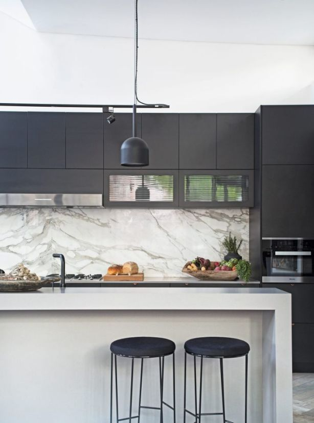 The kitchen features Dekton concrete-look benchtops and black Shaker profile cabinetry. Photo: Felix Forest
