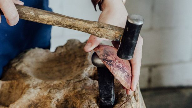Alison uses the tree stumps in her office when hammering her works. Photo: Andy Mullins
