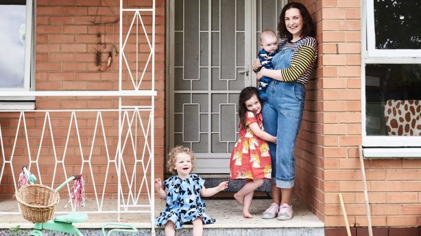 Natalie with her kids Hugo, Matilda and Stella, standing on the front porch of the 1960s Brighton rental property. Photo: Eve Wilson