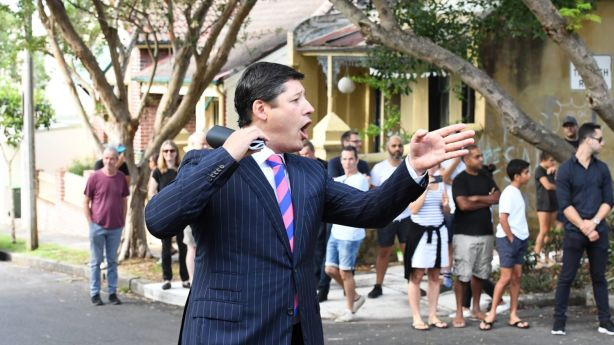 Auctioneer Scott Kennedy-Green took bids from two men at the auction. Photo: Peter Rae