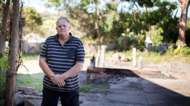John Sinclair with the charred remains of his Kenmore home, which burnt to the ground last November. Photo: Tammy Law