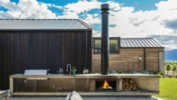 An Escea outdoor cooking fire completes this outdoor kitchen by Dravitzki Brown Architecture, it comes with an adjustable cooking plate for flame grilling. Photo: Escea
