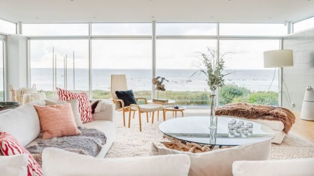Full-height windows showcase the point-blank water view in the living room. Photo: Sweden Sothebys International Realty