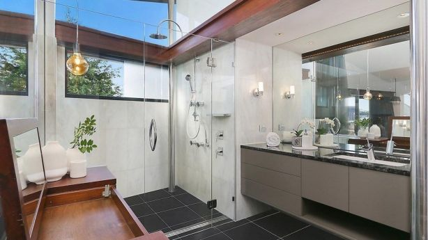 Bathroom bliss: Angles and glass cleverly used throughout fill the home with natural light. Photo: McGrath New Farm