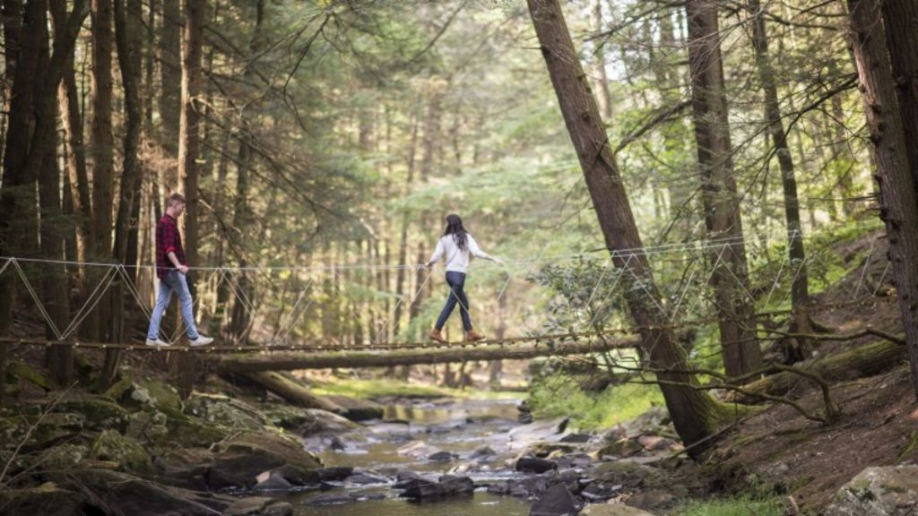 Brian Jacobs and Grace Kapin cross the suspension bridge that connects the bunkhouse side of Beaver Brook to its cabin side in Barryville. Photo: Theresa Ambrose, New York Times