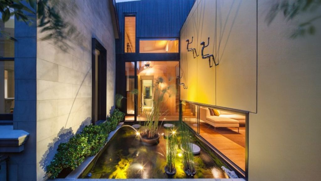 An exterior pond delineating the old and new fabric of a house by Nicholas Murray Architects. Photo: Ben Wrigley