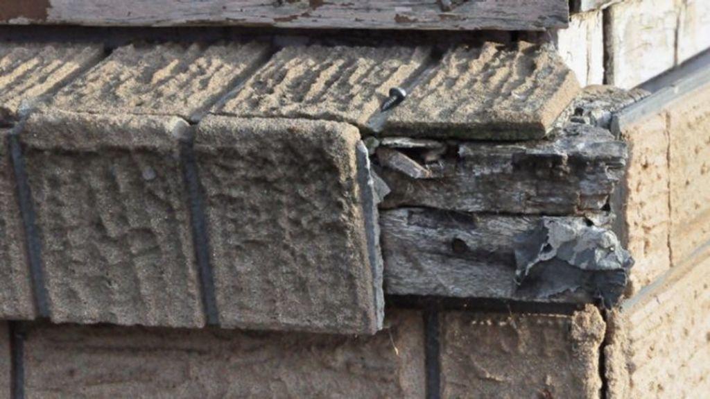 Close-up of imitation brick cladding on a broken exterior window ledge. Photo: Asbestos Awareness