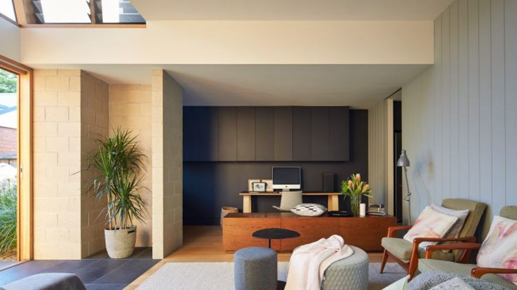 Dark colours link the living areas, while clever use of skylights allow the light inside. Photo: Peter Bennetts
