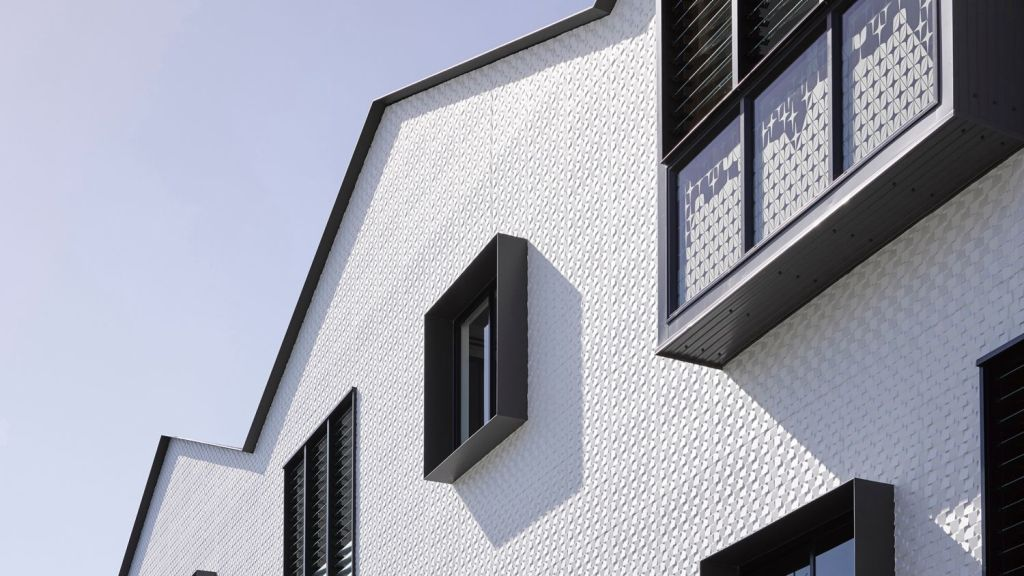 Protruding, black-trimmed bay windows in the white, texture-tiled frontage. Photo: Christopher Frederick Jones
