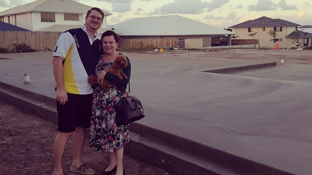 Keira and Steven Tunnah in front of slab that will soon be their new house in Mango Hill. Photo: Supplied