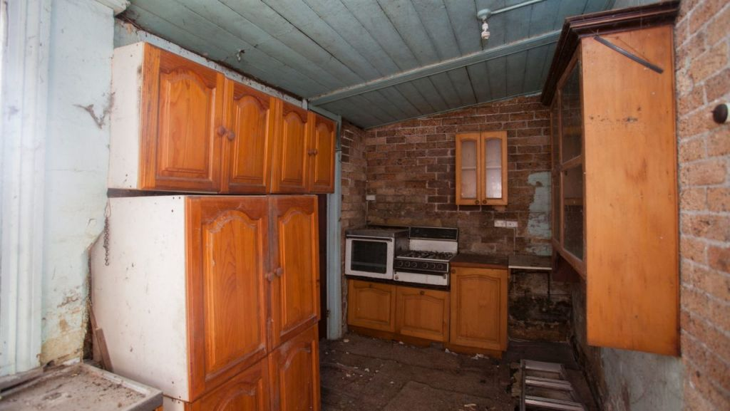 The back half of the property was in poor condition. This kitchen, unused for about five years, had missing floorboards, damaged walls and debris scattered throughout. Photo: Fiona Morris.