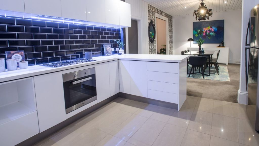 The sleek kitchen, meals and living area opens to an easy-care courtyard with a servery. Photo: SDP Media
