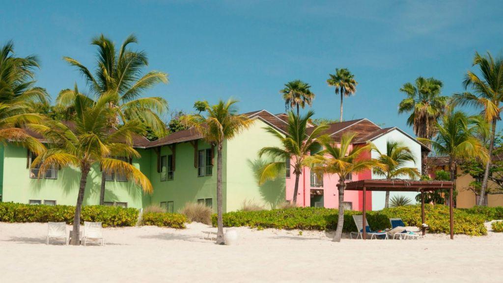 Pastel-coloured Caribbean homes on Grace Bay Beach, Turks and Caicos Islands. Photo: Alamy