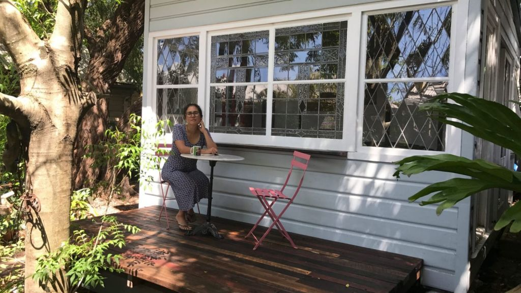 Vanessa Bates sitting on the deck of her writing studio.