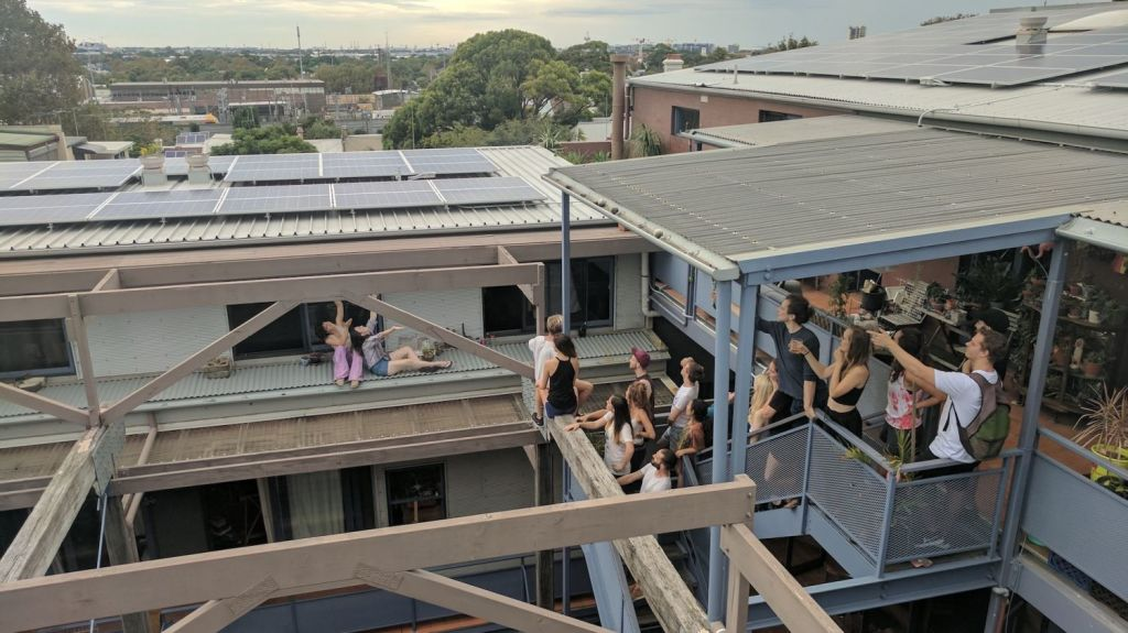 Students living at Stucco pose with the building's rooftop solar panels. Photo: Stucco