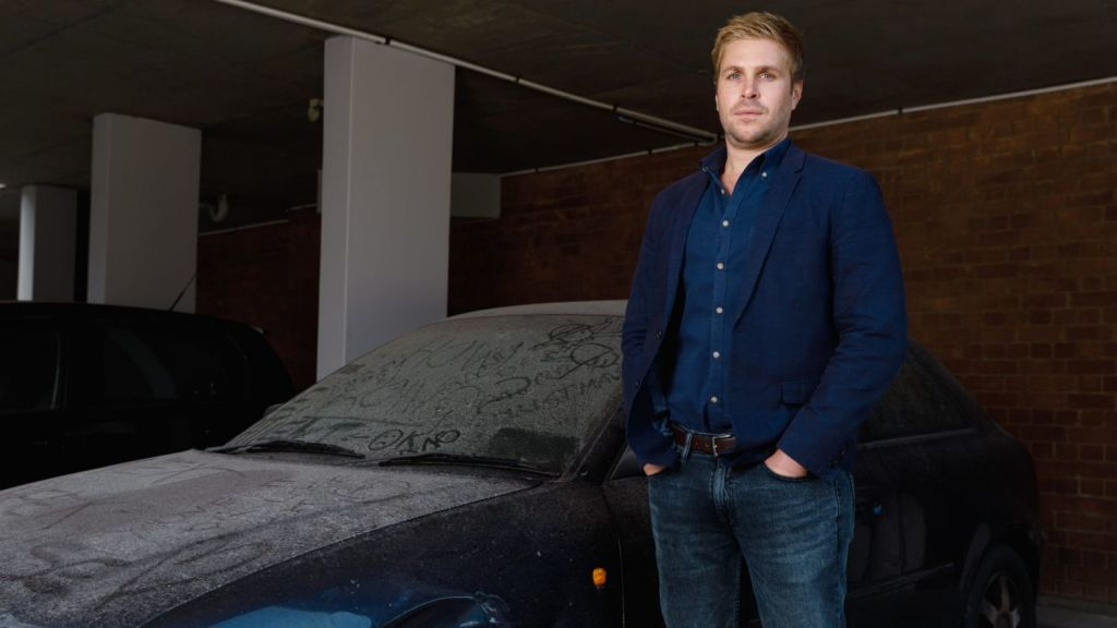 Philip Link, chairman of his owners corporation, has spent the last year fighting to remove a dumped car in the visitor parking of his apartment. Photo: Steven Woodburn