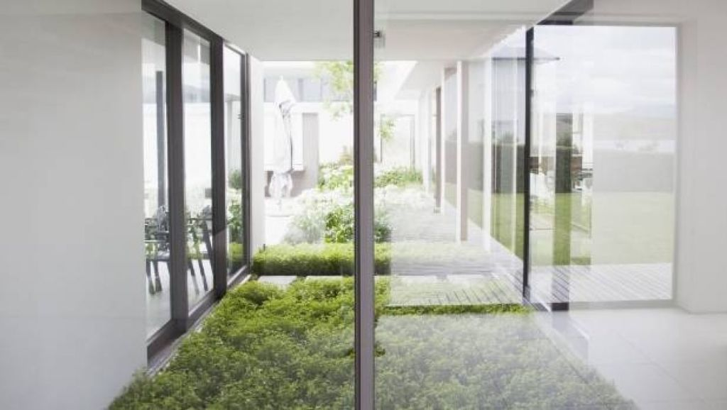 An indoor courtyard or garden surrounded by glass walls is a great way to bring light into areas with insufficient natural light. Photo: istock