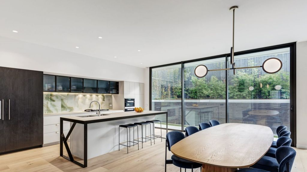 An adjoining dining area overlooks the backyard and pool, and has a very witty light fitting. Photo: Jellis Craig