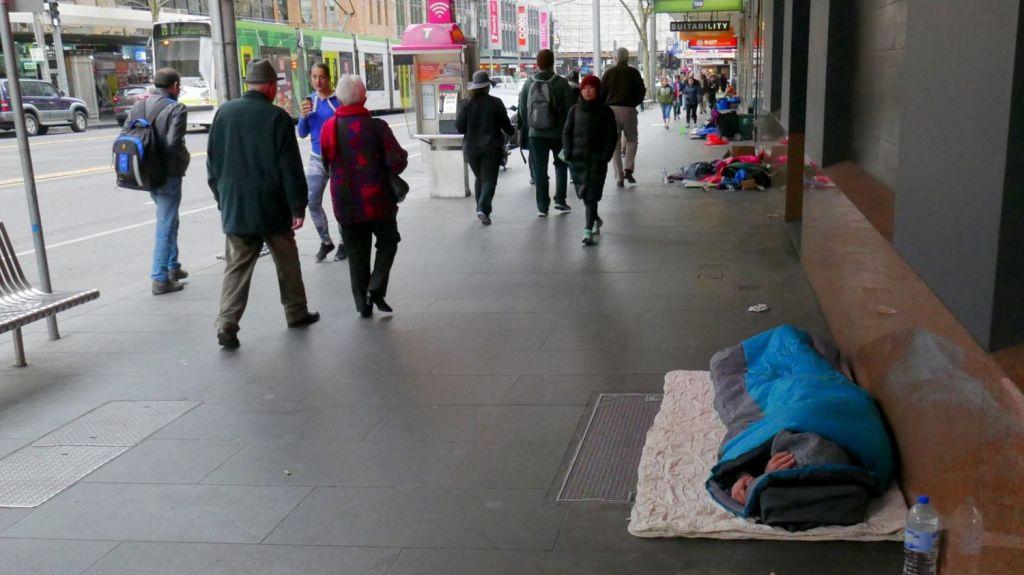 Homeless people sleep on the footpath in Elizabeth Street in Melbourne's CBD. Photo: Joe Armao