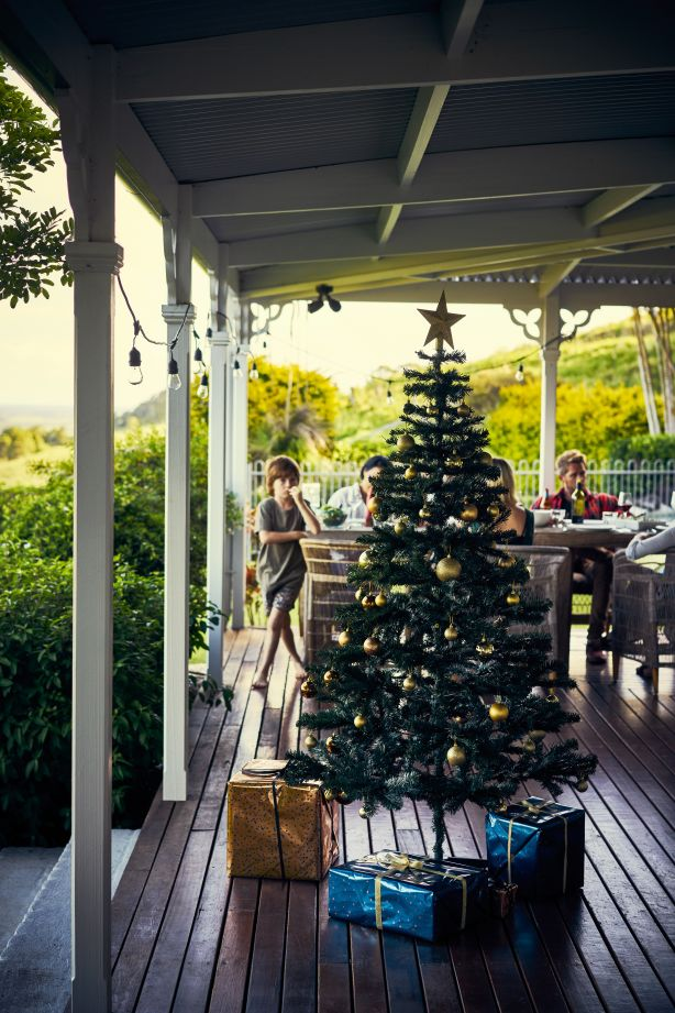 Shot of a Christmas tree standing outside on a porch with people in the background