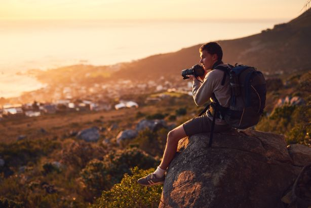 Photographer sitting on rock.