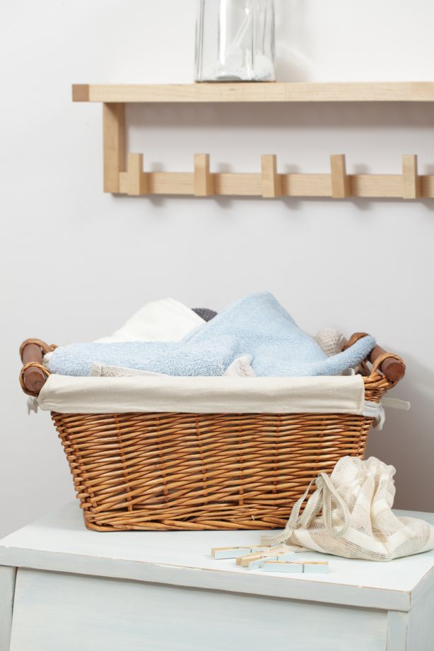 Basket with towels and clothespins in the bag in laundry room
