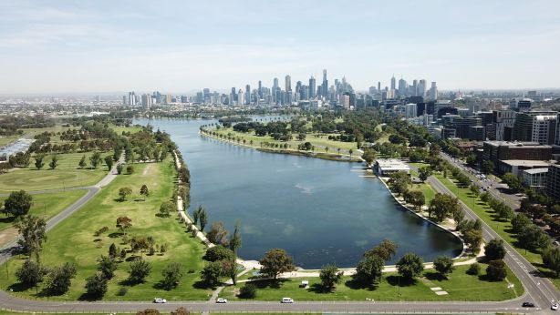 Aerial views of Albert Park Lake, Melbourne, with CBD skyline in the background.