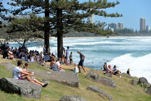 Crowds of people watch surfers taking on the huge swells hitting the coastline at Burleigh Heads.