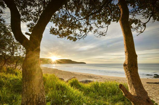 Sun rises over the horizon at Killcare Beach