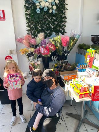 Chiswick_art_contest_winner_Ellie_Harrison_5_holdingher_colouring_book_prize_with_Samantha_Touma_Chiswick_Convenience_shop_owner_with_Ellie_s_friend_Emma_Manto_also_5_d9r8tp