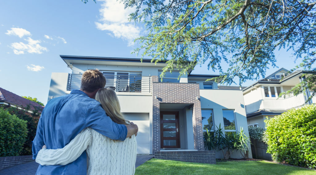 Couple looking at front of house from front yard
