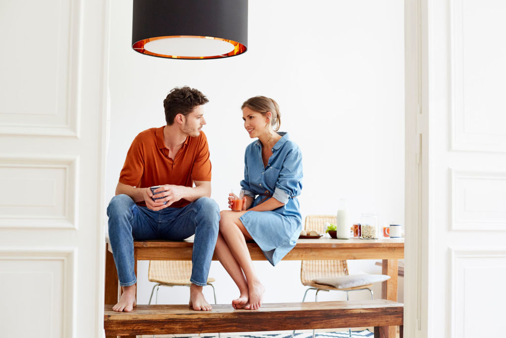 Young couple talking while sitting on breakfast table at home