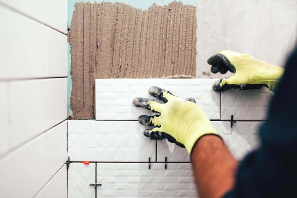 Worker installing small ceramic tiles on bathroom walls and applying mortar with trowel