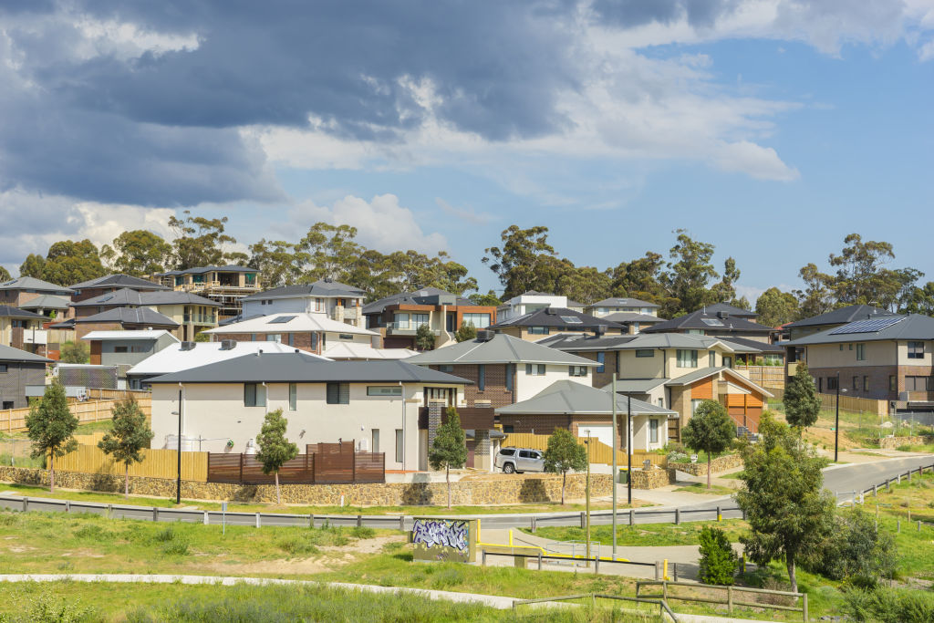 Row of new, modern suburban houses on the hill in Melbourne with trees during daytime.