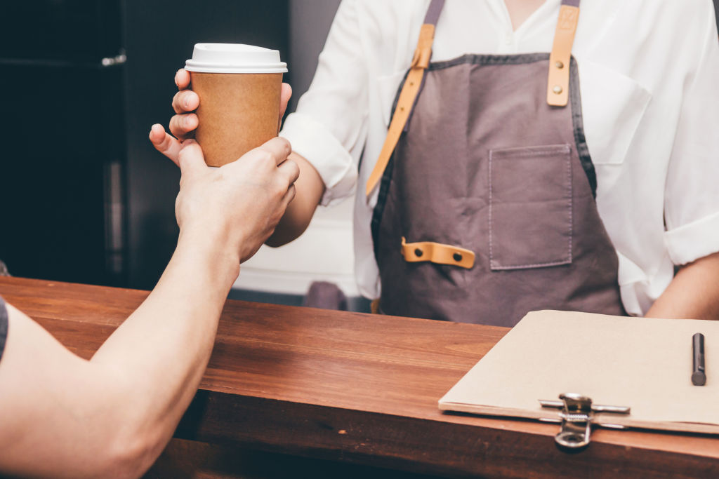 Barista giving coffee cup to customer at cafe