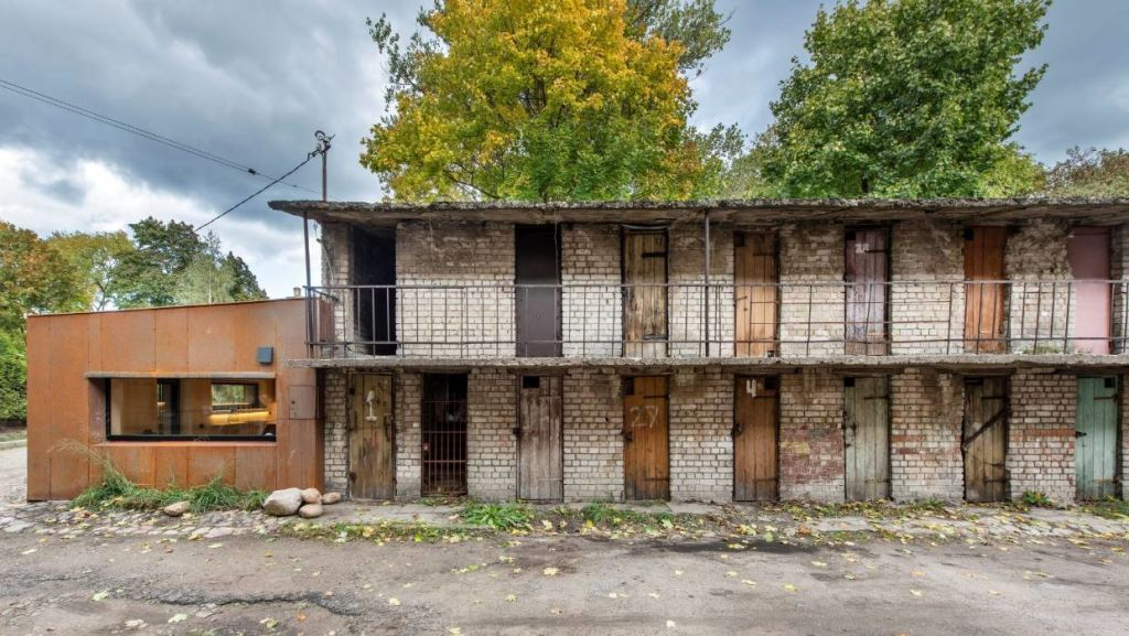 The rusted steel facade is a solid anchor at one end of the ramshackle building.