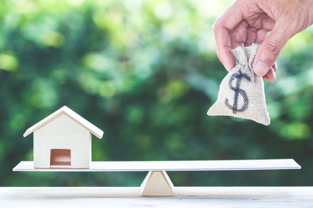 Balance home and money, home loan, reverse mortgage concept : A man hand put us dollar money bag into scales on table with green nature as background. Savings, investment, loan for plan in the future.