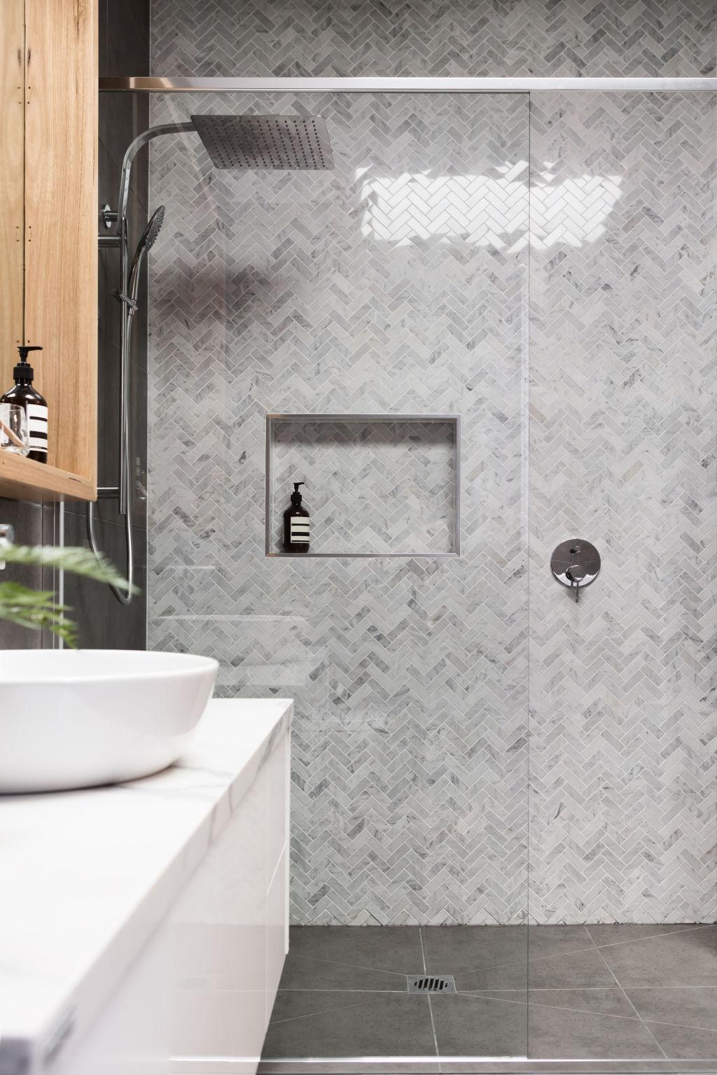 Rain shower with luxury herringbone marble feature tile wall.