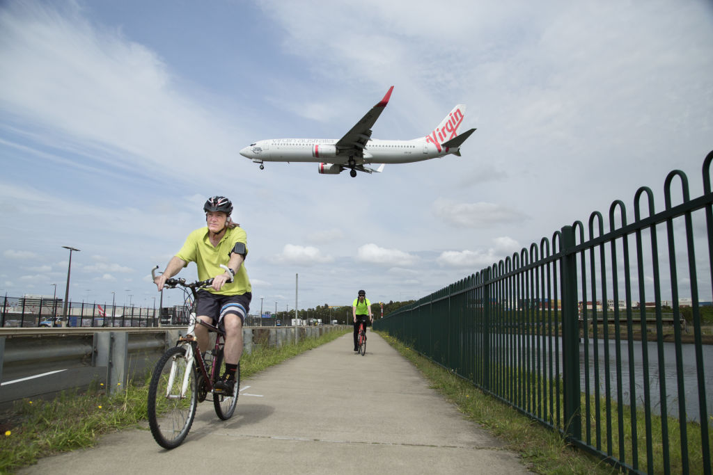 An airplane flies over cyclists in Mascot