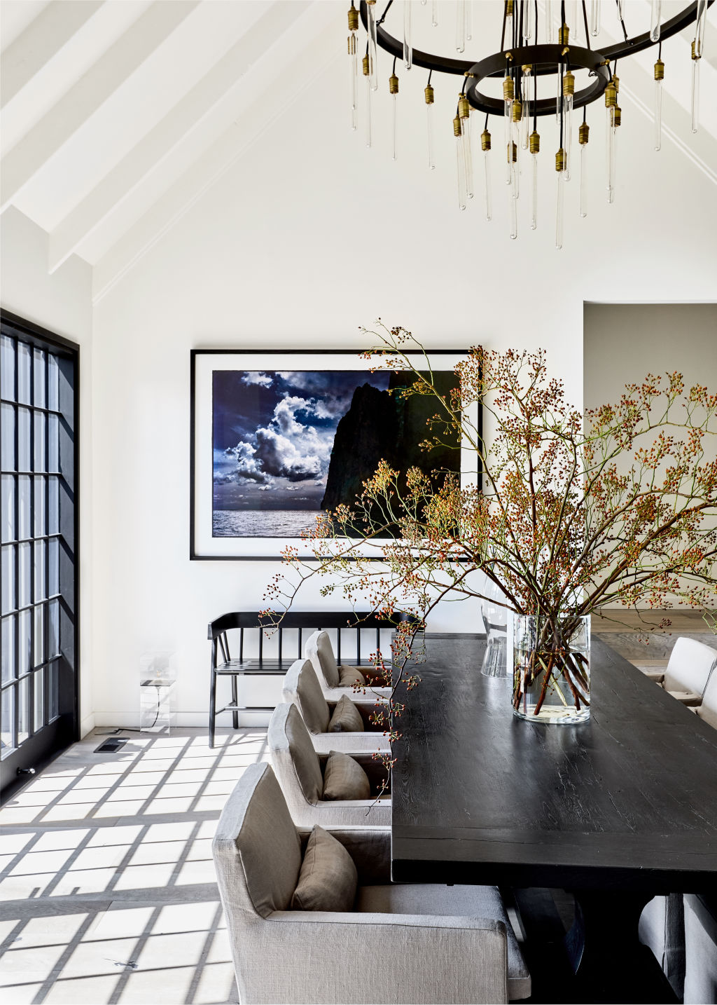 'We love the idea of the dining table working as an entrance table too', Chyka tells, 'I always fill the large vase with whatever is in seasonally, and because the space is neutral it can take any colour or style.' The photo on the wall is of Capri by Bill Henson. Light, table, and chairs are from Restoration Hardware. Black bench from House of Orange. Styling: Lucy Feagins
