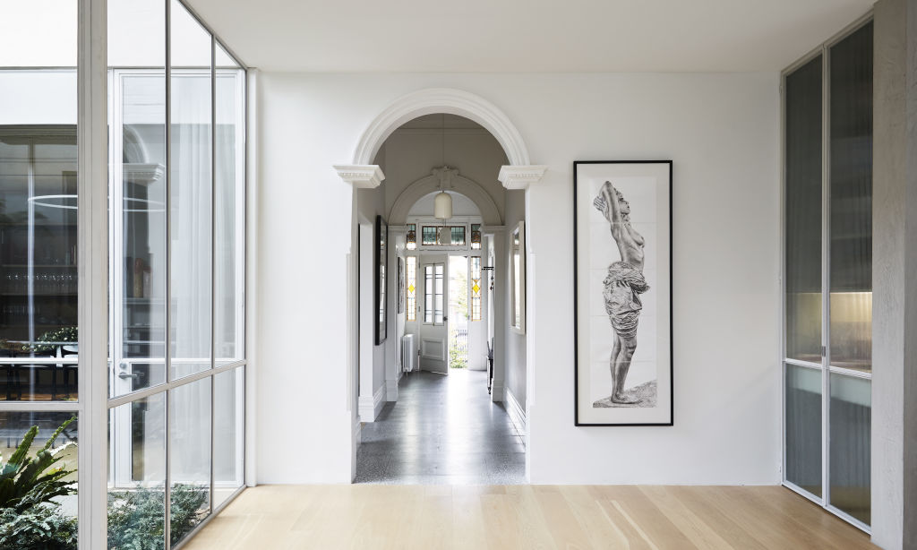 The renovated heritage home of Cara Bodsworth in Armadale. Looking through the entrance hall to the front door. Artwork by Pietro Capogreco. Listone Giordano flooring. Pendant lights by Porcelain Bear. Styling: Annie Portelli.