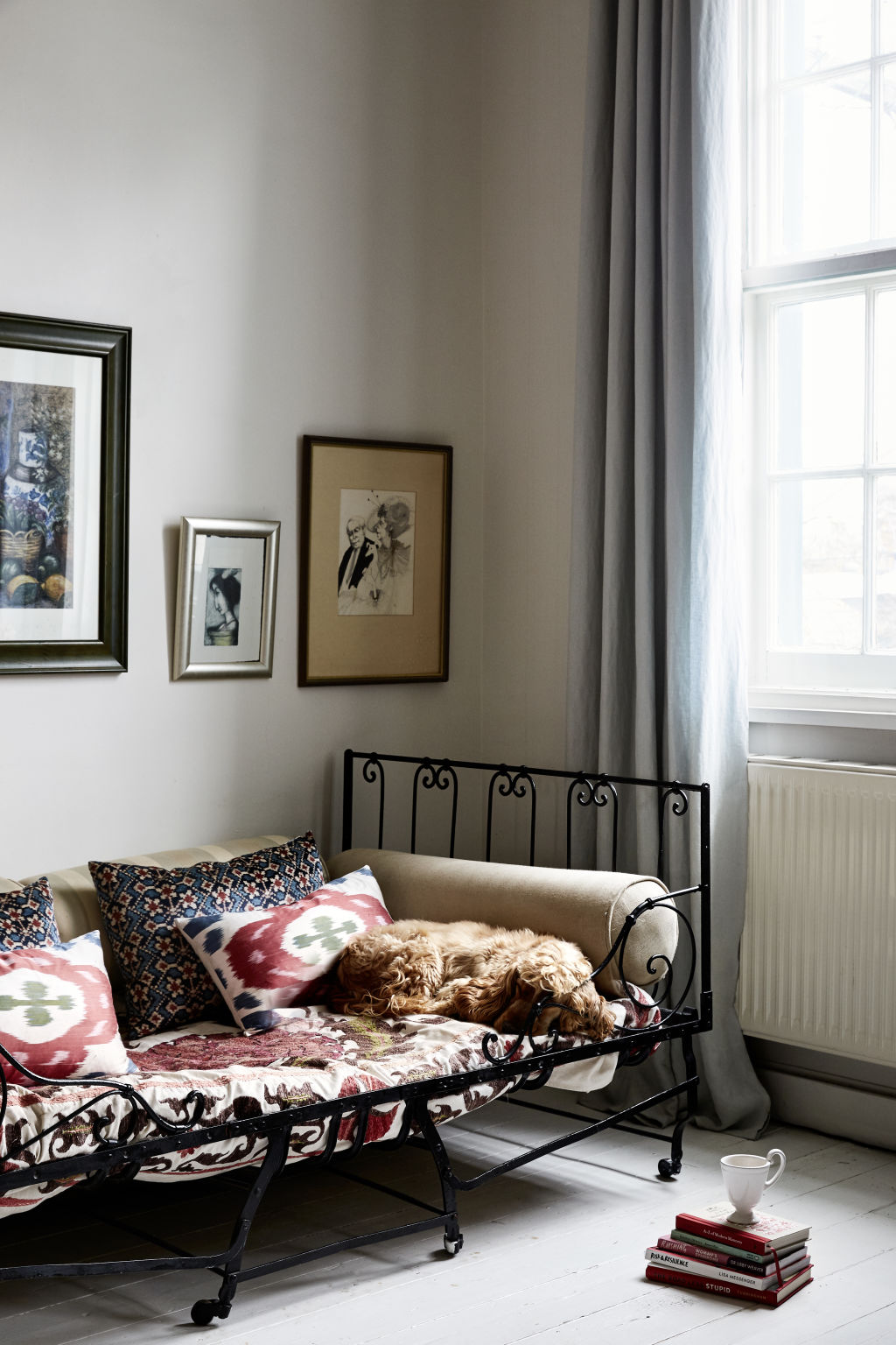 Early French folding bed purchase in L'Isle-sur-la-Sorgue, Tigger's favourite antique shopping spot in France. Almaty Velvet black cushions by Carolina Irving. Painting by Tigger and Sue McCartney Space, 'I love her wicked sense of humour'. Styling: Annie Portelli.