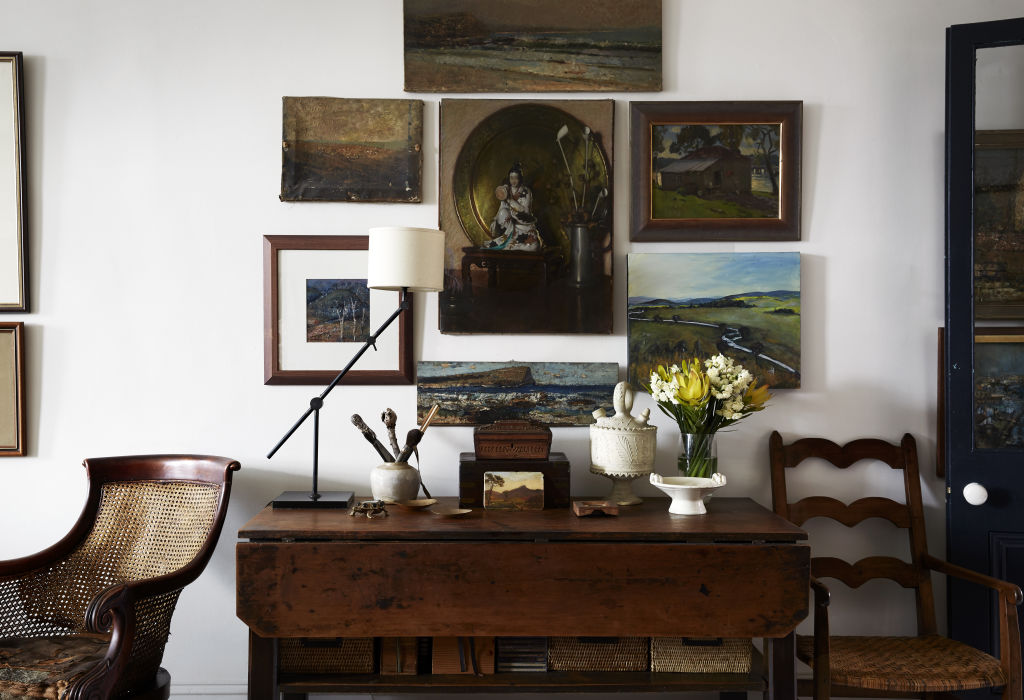 Salon wall of paintings by Tigger alongside those by her great grandfather, Bernard Hall. The studio table and chair are also his. Styling: Annie Portelli.